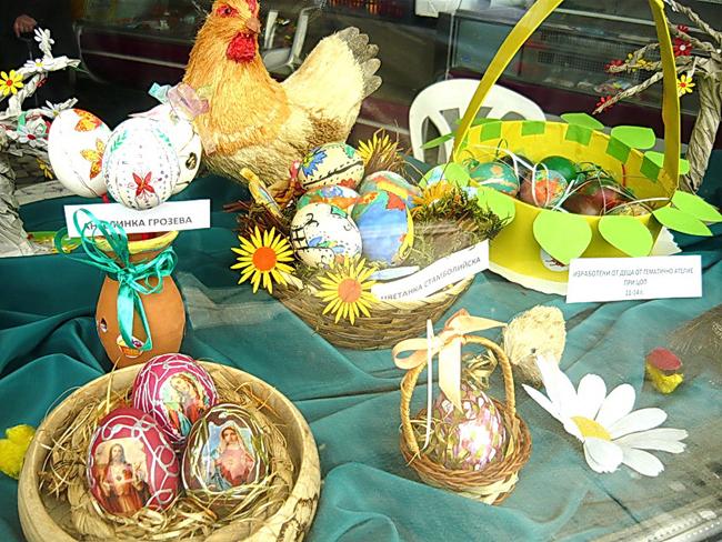 """На Велики четвъртък служителите от читалище """"Рила-1898"""" в Долна баня по традиция подредиха голяма изложба на великденски яйца, която украси витрината на централния хранителен магазин на местната потребителна кооперация """"Напредък"""". […]"""