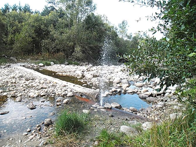 """Фотореплика """"Истински фонтан изригва от водопроводна тръба в коритото на Искъра на мястото в Лаго, където водопроводът пресича реката. Хора слагат камъни, за да запушат дупката, но нищо не става. […]"""